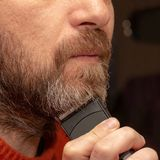 A man cuts his gray beard trimmer. Close-up stock photography