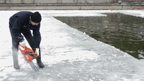 Man Cuts Ice With Chainsaw on the Frozen Lake stock footage