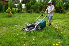 The man cuts the lawn with an combustion mower in the backyard garden. Cutting high grass with a large hand-driven combustion lawn mower. Man during work stock photography