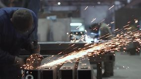 A man cuts metal with a circular saw, welding works are carried out in the background. Sparks from working with metal stock video footage