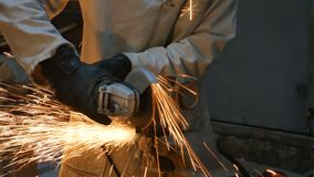A man cuts metal with a grinder in his workshop. A man`s hobby. 4K.  stock video footage