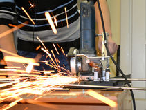 Man cuts metal and sparks Stock Images