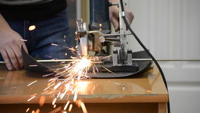 Man cuts metal and sparks. Worker man cutting a metal pipe in two pieces and lot of sparks flying straight into the camera close-up stock video