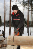 Man cuts off beam using chainsaw for future log cabin. Royalty Free Stock Photos