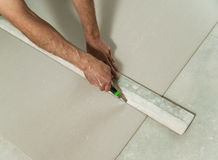 Man cuts off a piece of drywall Stock Images