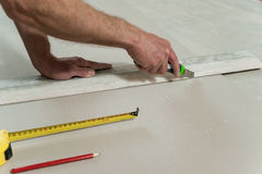 Man cuts off a piece of drywall Stock Photo