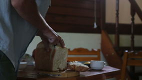 Man cuts off white bread crust. And smelling it stock footage