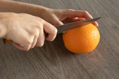 Man cuts an orange with a knife on a wooden surface stock image