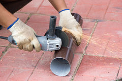 Man cuts pipe with an angle grinder closeup Royalty Free Stock Photography