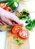 Man cuts ripe tomatoes for summer vegetable salad Stock Photo