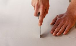 Man cuts a sheet of heat insulating and sound proof material. With a stationery knife stock photo