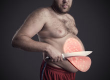 Man cuts a slice of sausage from his belly Royalty Free Stock Images