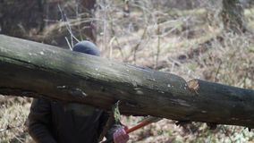 The man cuts a tree with an ax in the forest, which blocked the road. The man cuts a tree with an ax in the forest, which blocked the road stock video