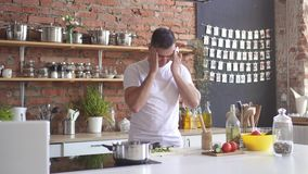 Man cuts vegetables in the kitchen and experiences a sharp headache, he grabs his head stock footage
