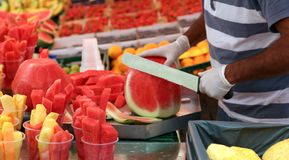 Man cuts watermelon with a large and sharp knife to prepare frui. Skilled fruit-veggie cuts watermelon with a large and sharp knife to prepare fruit salad for Stock Images