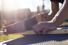 Man cuts a wooden product with a carpentry hand saw, in the sunshine on a warm summer day. Outdoors royalty free stock image