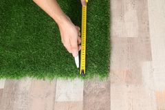 Man cutting artificial grass carpet indoors, top view. Space for text stock photography