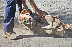 Man Cutting Asphalt. A worker cutting the edge on asphalt getting ready to do a paving job Stock Photo