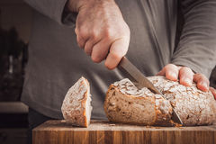 Man cutting bread Stock Images