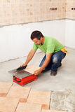 Man cutting ceramic floor tile Royalty Free Stock Photos