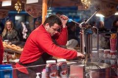 Man cutting churros at the christmas market Royalty Free Stock Images