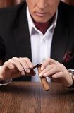 Man cutting a cigar. Successful mature man in formalwear cutting Royalty Free Stock Photography