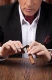 Man cutting a cigar. Successful mature man in formalwear cutting. A cigar Royalty Free Stock Photography