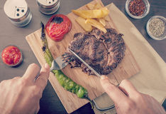 Man cutting and eating a grilled beef steak Royalty Free Stock Photography