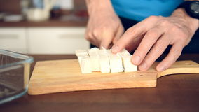 Man cutting feta cheese for salad stock video footage