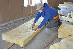 Man cutting fiberglass insulation Stock Photos