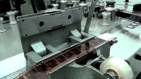 Man cutting film on retro machine cutter for movie film. This is footage of man cutting film on retro machine cutter for movie film stock footage