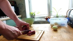 Man cutting fresh fillet meat pork on pieces to cook shashlik, hands closeup. He cutting on wooden board kitchen table. stock footage