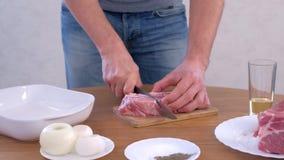 Man cutting fresh fillet meat pork on pieces to cook shashlik, hands closeup. stock footage