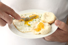 Man cutting into fried eggs Royalty Free Stock Image
