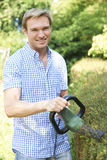 Man Cutting Garden Hedge With Electric Trimmer Royalty Free Stock Photography