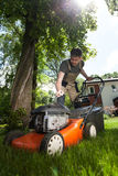 Man cutting grass in his yard Royalty Free Stock Photo