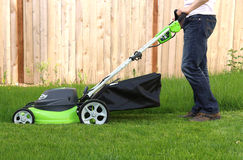 Man cutting the grass with lawn mower Royalty Free Stock Images