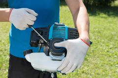 The man cutting a grass with the lawn mower. Closeup stock photography