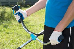 The man cutting a grass with the lawn mower. Closeup stock images