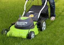 Man cutting the grass with lawn mower Stock Photos