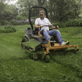 Man cutting grass on lawnmower Stock Photography