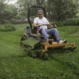 Man cutting grass on lawnmower Stock Photography