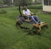 Man cutting grass on lawnmower Stock Photo