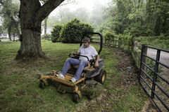 Man cutting grass on lawnmower Royalty Free Stock Image