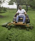 Man cutting grass on lawnmower Stock Photos