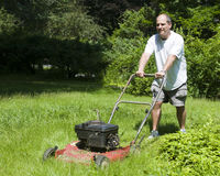 Man cutting grass at suburban house royalty free stock photography