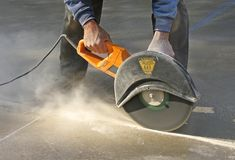 Man cutting groove in concrete slab. Man cutting control groove in concrete slab with a circular saw royalty free stock photography