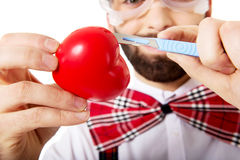 Man cutting heart model with scalpel. Royalty Free Stock Image