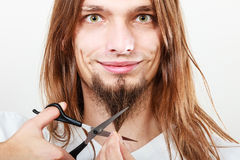 Man cutting his beard. Cut and shave concept. Young man with long beard holding scissors. Boy cutting hair on chin Stock Images