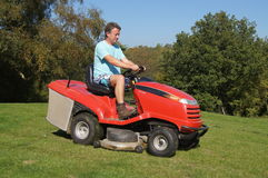 Man cutting his grass. Man driving a sit on lawn mower cutting the lawn in his garden Royalty Free Stock Photo